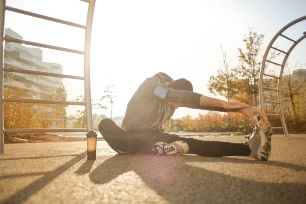 Man stretches before running for summer exercise